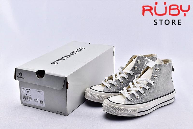 Đôi giày Converse x Fear of God Essentials màu xám cạnh chiếc hộp