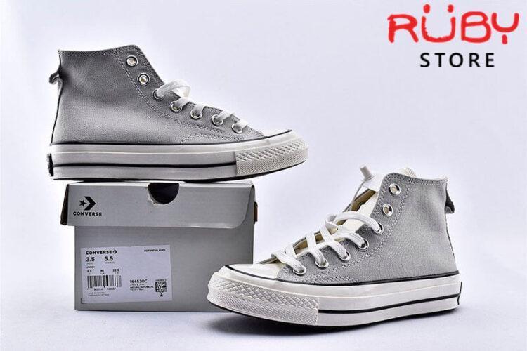 đôi giày Converse x Fear of God Essentials màu xám đặt song song bên chiếc hộp