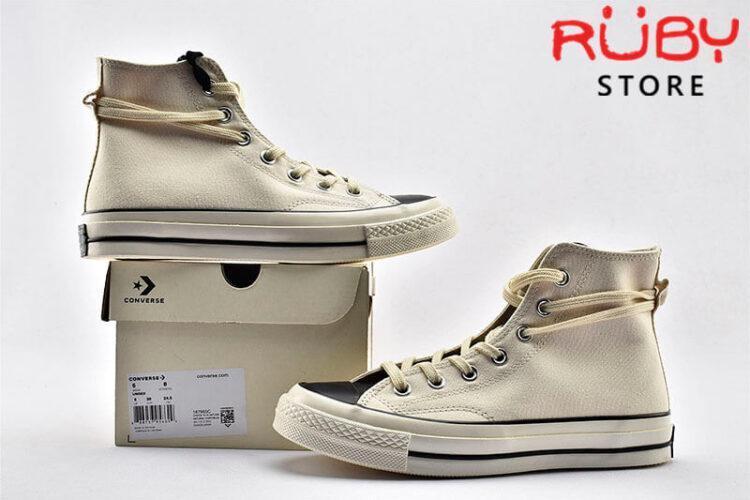 Đôi giày Converse x Fear of God Essentials màu trắng song song cạnh chiếc hộp